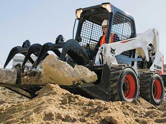 Bobcat M2 series skid-steer loader lifting rocks