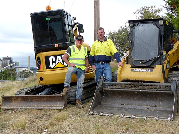 Ron Horner and Andy Sheather with the Cat excavator/skid steer combo and Wallerawang Power Station in the background.