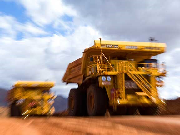 Komatsu mining trucks moving at speed