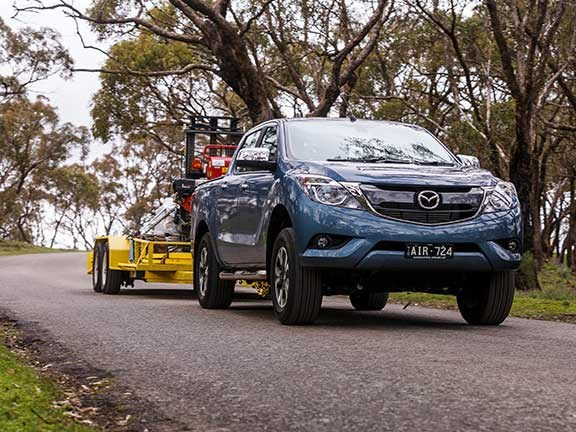 Mazda BT-50 towing excavator downhill