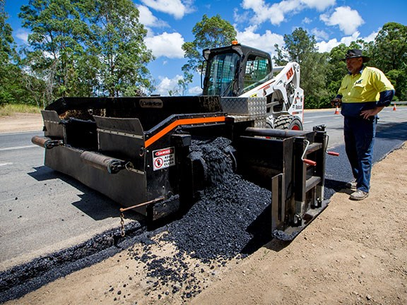 The ShoulderMaster road paver attachment for skid steer loaders.