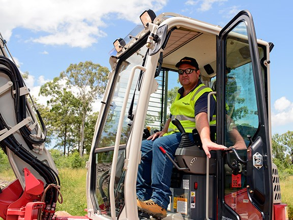 Reviewer Evarn Covich in the cab of the the Takeuchi TB280FR excavator.