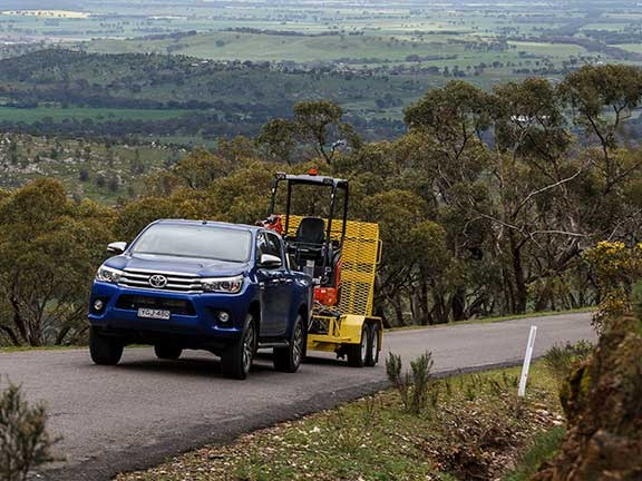 Toyota Hilux ute towing excavator on trailer