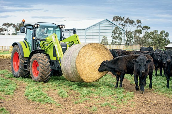 The Arion 440 lifting a hay bale