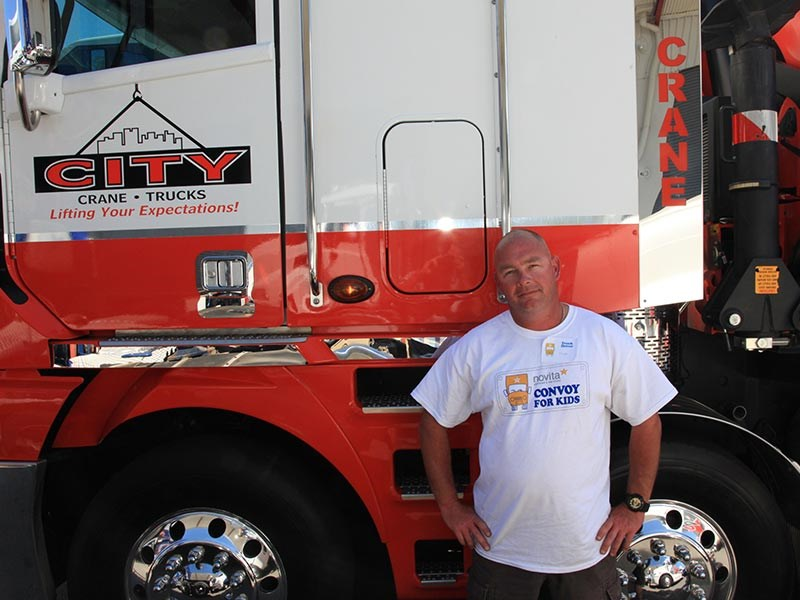 Matthew Mundy who drives for City Crane Trucks proudly standing in front of the company's Argosy.