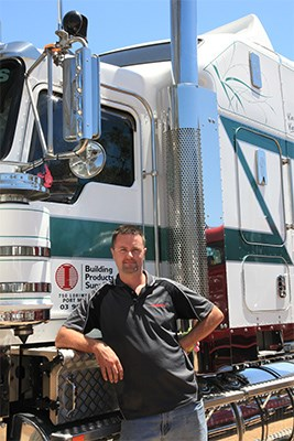 John Wilson in front of a Building Products Supplies 2014 Kenworth T909.