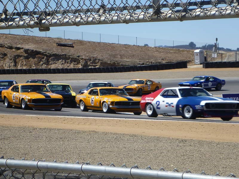 AMC leads a pair of Grabber Orange Boss Mustangs at Laguna Seca