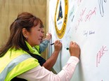 Logistics manager Marifé Gregory places her artistic signature on the Sika Safety banner