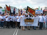 TWU supporters march outside of an ALDI store