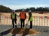 Toll Group's Michael Byrne, centre, breaks ground at the Arundel site, alongside Logos' John Marsh and Kelly Xu of Partners Group)