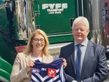 "David Fyfe, the father of Fremantle Dockers' captain Nat, bears a gift to ""passionate Dockers supporter"" Rita Saffioti"