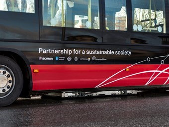 Scania electric bus charges at the stop