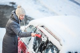 Woman scraping ice off her car