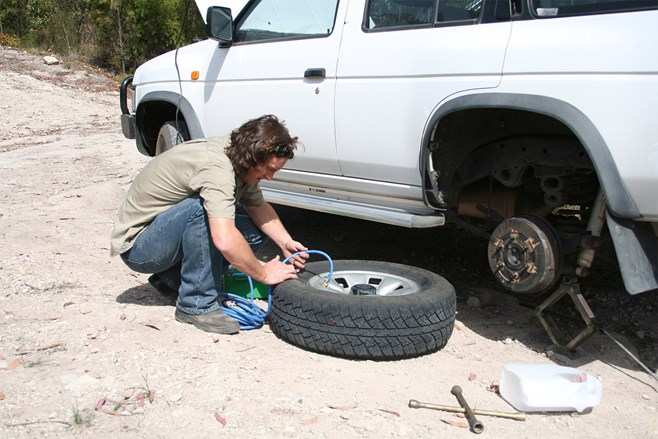man fixing tyre puncture