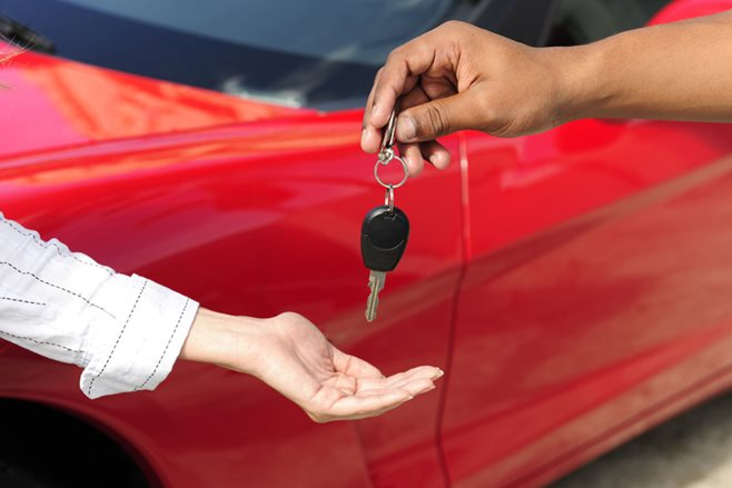 New car buyer collecting keys from car dealer