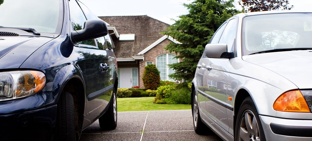 cars parked outside of suburban house