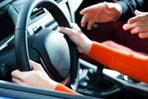 How far should you sit from the steering wheel?