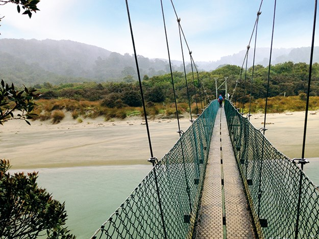 Crossing the suspension bridge to Maori Bay.jpg
