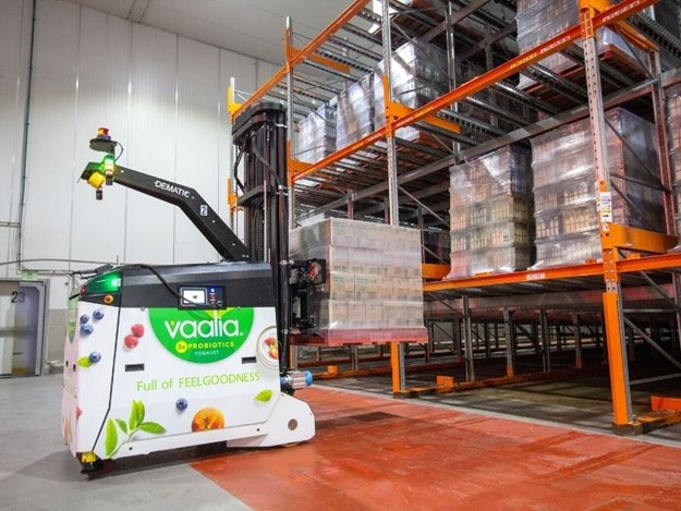 The AGVs retrieve pallets from inbound conveyor system from production and feed them into order buffer lanes in gravity racking