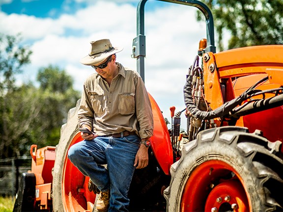 farmer stands beside his tractor