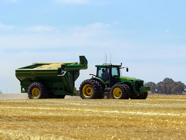 A tractor takes part in barley harvesting, alongside a combine harvester and chaser bin near Lock, on South Australia's Eyre Peninsula. Image courtesy Alamy.