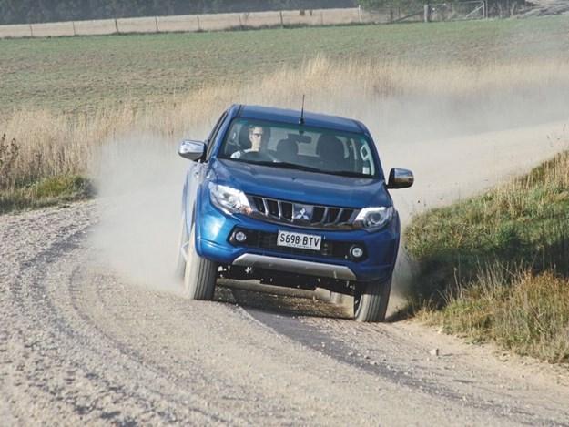 A Mitsubishi Triton driving on a dirt road