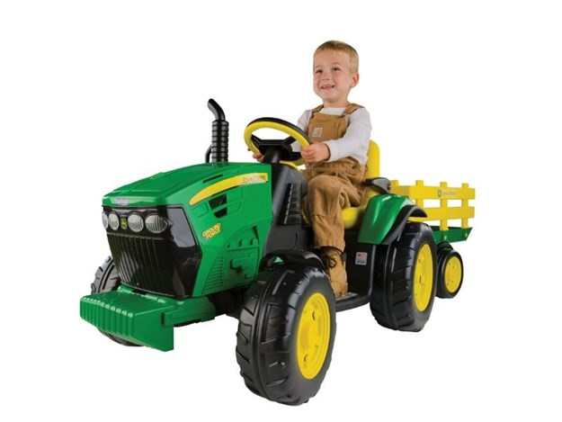 The JOHN DEERE 12V GROUND FORCE TRACTOR AND STAKE WAGON