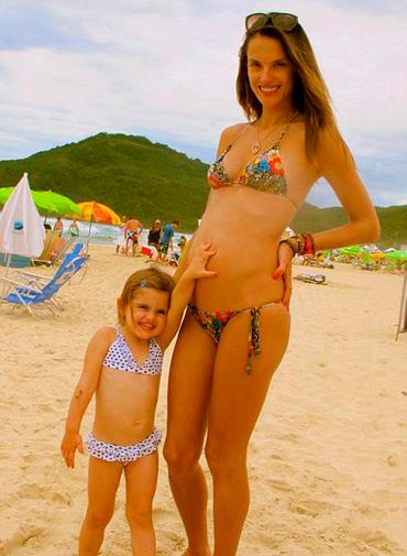 Alessandra's daughter rubs her bump on the beach.