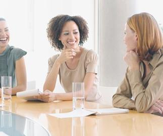 three women gathered around table conversing, getty images