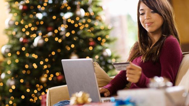 women with credit card near christmas tree, thinkstock