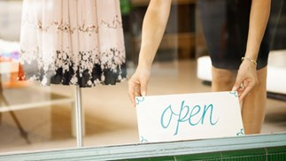 women putting an open sign in shop window, thinkstock