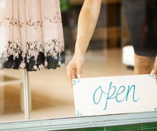 women putting an open sign in shop window, thinkstock