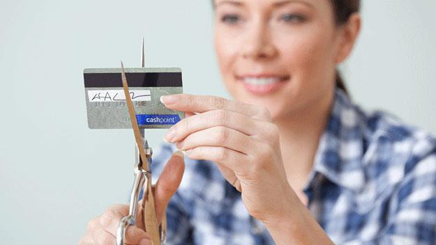 woman cutting up her credit card, Getty Images