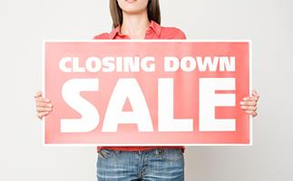 Woman holding up closing down sale sign, getty