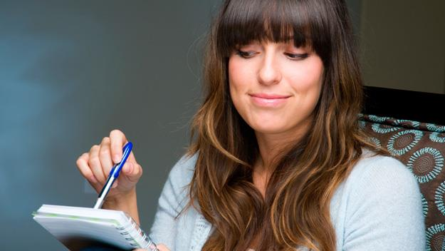 brunette woman with notepad and pen