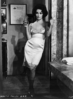 British-born Elizabeth looks every inch the sex siren of the 60s as she stands in a doorway holding a glass in a still from the film, *BUtterfield 8* directed by Daniel Mann.  Photo by: MGM Studios/Getty Images