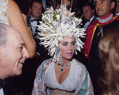 Elizabeth Taylor attends a social function in 1967 wearing an elaborate headdress of pearls and fake flowers, a jewelled dress and an emerald necklace.  Photo by Keystone/Getty Images