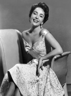Smiling happily for a promotional portrait in 1952, Elizabeth Taylor looks radiant wearing a sleeveless lace brocade dress.  Photo by Hulton Archive/Getty Images
