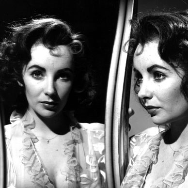 Elizabeth Taylor, British film actress strikes a reflective pose in 1954.  Photo by Baron/Getty Images