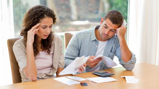 distressed couple looking at paperwork