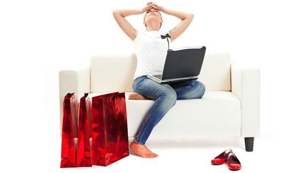 distressed woman with laptop and red shopping bags