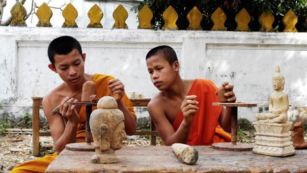 Novice monks learn how to sculpt Buddha heads from wood.