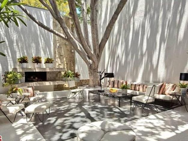 The home has an interior courtyard sheltered by a large tree.