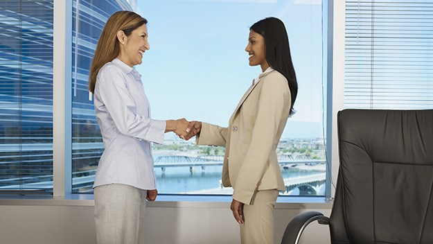 Women shaking hands in office