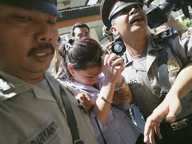 Being escorted by police following her trial. Photo: Getty Images