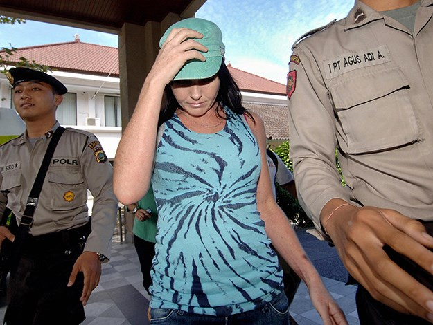 Escorted by two policemen as she leaves a beauty salon in Denpasar. Photo: escorted by two policemen as she leaves a beauty salon in Denpasar on Bali island on July 2, 2008.