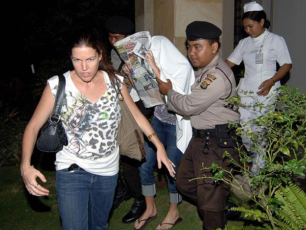 Schapelle covers her face with a newspaper as policemen escort her back to jail from a hospital in Denpasar. Photo: AFP/Getty Images