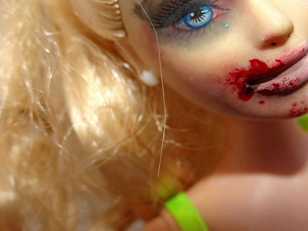 The artist blackened the doll's eyes and bloodied her lips to create the images. © Samantha Humphreys.