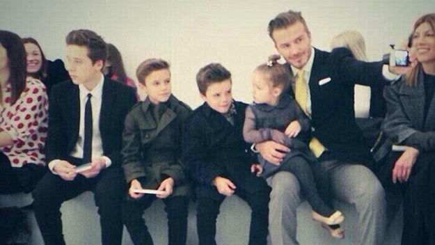 David Beckham snaps a family selfie as he sits front row with his children, Brooklyn, Romeo, Cruz and Harper.