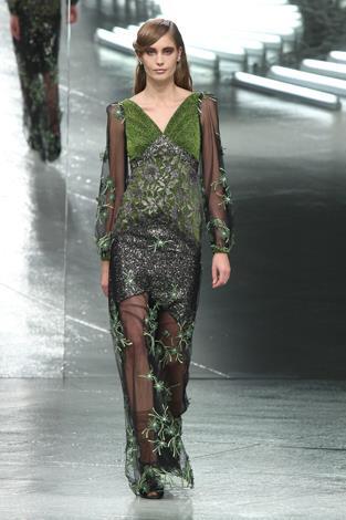 A model walks the runway during the Rodarte fall 2014 fashion show in a sheer outlandish design.
